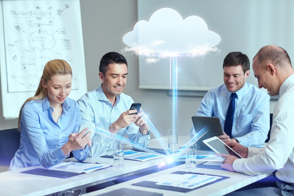 Four co-workers having data beamed to them from the cloud