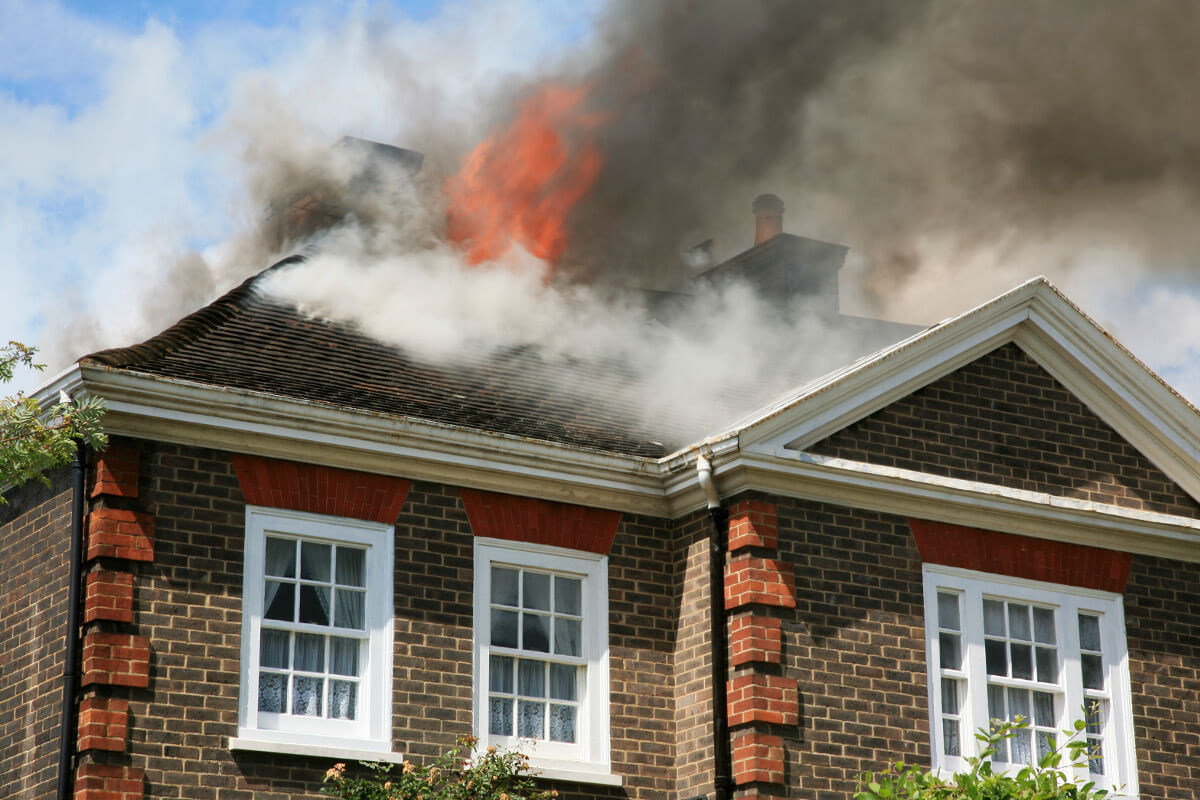 Fire and smoke on roof of brown, single-story brick house