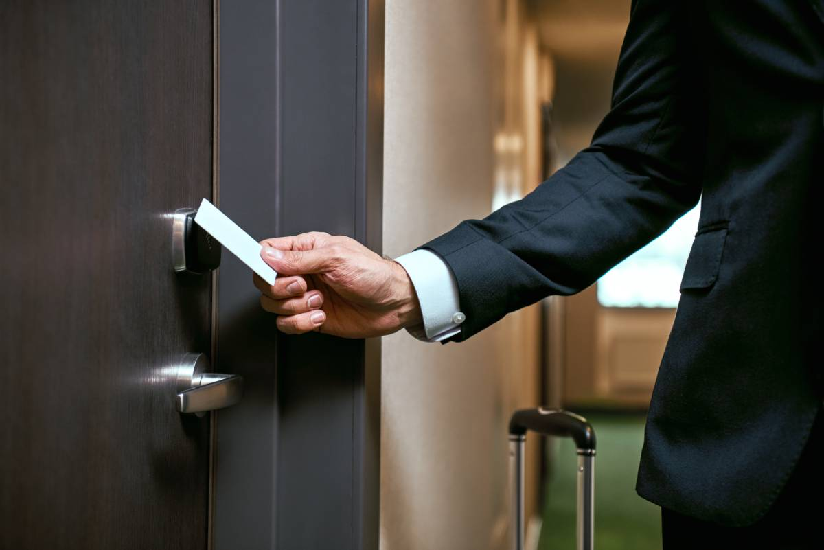 A hotel employee opening a door with a key card