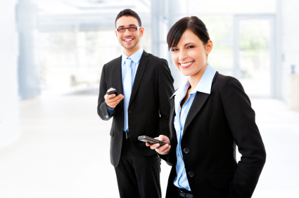 Two young business people holding mobile devices and smiling